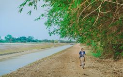 KANCHANABURI THAILAND - APRIL 4: Niet ge?dentificeerde jonge vrouw die een fiets berijden op grintweg langs het irrigatiekanaal i stock afbeeldingen