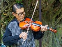 Kanchanaburi Thailand - December 25,2516: Asiatisk musikervioli Royaltyfria Bilder