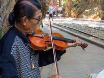 Kanchanaburi Thailand - December 25,2516: Asiatisk musikervioli Royaltyfri Foto