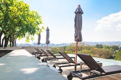 Kanchanaburi, Thailand - February 20, 2019 : Modern and simply design chaise lounge and swimming pool on the hotel roof top with. Mountain view royalty free stock images