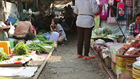 KANCHANABURI, THAILAND - FEBRUARY 2014: Train passing through market stock video footage