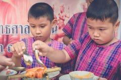 KANCHANABURI THAILAND - JULI 24: Den oidentifierade läraren och studenter sammanfogar smältande gjutit stearinljuserbjudande till fotografering för bildbyråer
