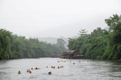 Kanchanaburi Thailand - Juli 06 2016: Turister som blir på semesterorten som spelar aktivitet som svävar bad i flodkwai arkivbild