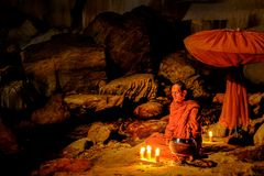Buddhist monk doing meditation in cave. Kanchanaburi, Thailand - July 15, 2011: Buddhist monk sitting with alms bowl, lighten candle and long-handles umbrella to