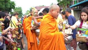 Kanchanaburi, Thailand - July 17, 2019 : Tourist are offering food to the Monks in Mon Bridge at Sangklaburi District. Kanchanaburi stock video footage