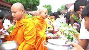 Kanchanaburi, Thailand - July 17, 2019 : Tourist are offering food to the Monks in Mon Bridge at Sangklaburi District. Kanchanaburi stock video