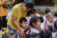 KANCHANABURI THAILAND - JULY 26 : Unidentified teacher and students waited for time to go to temple in traditional lent candle fe royalty free stock image