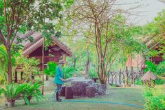 KANCHANABURI-THAILAND, March 2, 2019 : Unidentified Senior man watering plants with hose and working in garden at his home on. March 2,2019 in Kanchanaburi royalty free stock photo