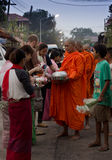 Kanchanaburi, Thailand - March 16, 2014: Villagers give food offering to a monk royalty free stock photos