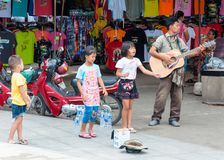 Kanchanaburi, Thailand - May 23, 2014: Unidentified children sing and adult play guitar on the street to obtain money on May 23, Royalty Free Stock Photos