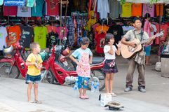 Kanchanaburi, Thailand - May 23, 2014: Unidentified children sing and adult play guitar on the street to obtain money on May 23, Stock Images