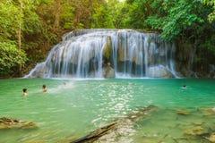 KANCHANABURI THAILAND - 16. NOVEMBER: Viele Touristen stehen im Wasserfall und im Nehmen einer Dusche an Erawan-Wasserfall 16,201 stockfoto