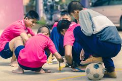 KANCHANABURI THAILAND - SEPTEMBER 20 : Unidentified students he. Lp to build a sepak takraw field border on the cement floor on September 20,2018 at royalty free stock images