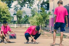 KANCHANABURI THAILAND - SEPTEMBER 20 : Unidentified students he. Lp to build a sepak takraw field border on the cement floor on September 20,2018 at stock photos