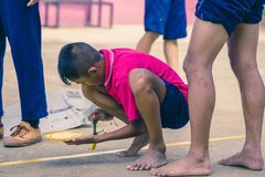 KANCHANABURI THAILAND - SEPTEMBER 20 : Unidentified students he. Lp to build a sepak takraw field border on the cement floor on September 20,2018 at stock images