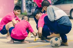 KANCHANABURI THAILAND - SEPTEMBER 20 : Unidentified students he. Lp to build a sepak takraw field border on the cement floor on September 20,2018 at royalty free stock image