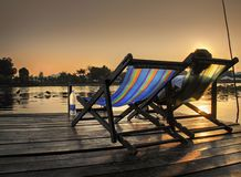 Kanchanaburi, Thailand. A Woman Relaxes In a deck chair At sunset . Next to the river Kwai royalty free stock photography