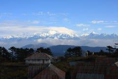 Kanchenjunga与树、蓝天和云彩的山景 库存图片