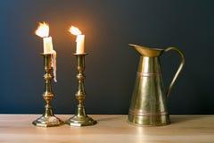 Kandelaber med bränningstearinljus och den antika kruset i inre Arkivbild