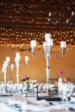 Kandelaber med stearinljus på dekorerade tabeller för bröllopmottagande Fotografering för Bildbyråer