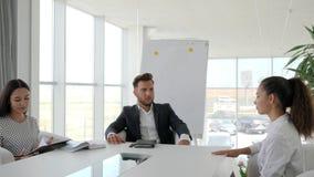 Kandidaat tijdens baangesprek in groot bedrijf in wit en ruim bureau, dialoog over baan met secretaresse en werkgever stock footage