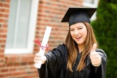 Kandidat: Kvinnlig student Gives Graduation Thumbs upp royaltyfri fotografi