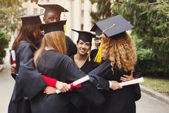 Kandidater som har gruppkramen på avläggande av examendag arkivfoton