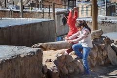Two Iranian girls playing on the street in rock village Kandovan. Iran. Kandovan, East Azerbaijan province, Iran - March 16, 2018: Two Iranian girls playing on royalty free stock photos