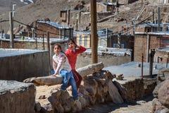 Two Iranian girls playing on the street in rock village Kandovan. Iran. Kandovan, East Azerbaijan province, Iran - March 16, 2018: Two Iranian girls playing on stock images