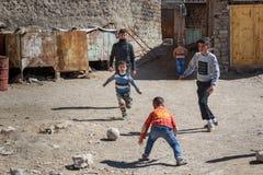 Young Iranian boys play football on the street in rock village Kandovan. Iran. Kandovan, East Azerbaijan province, Iran - March 16, 2018: TYoung Iranian boys royalty free stock photography