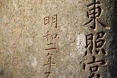 Kandschi-Symbole schnitzten im Stein Stockfotografie