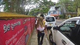KANDY, SRI LANKA - EM FEVEREIRO DE 2014: Equipe a menina loura pequena levando em suas partes traseiras quando as caminhadas trag video estoque