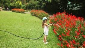 KANDY, SRI LANKA - FEBBRAIO 2014: Fiori d'innaffiatura della bambina nei giardini botanici a Kandy I giardini attirano 2 milione  stock footage