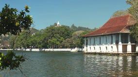 KANDY, SRI LANKA - FEBRUAR 2014: Ansicht des Hauses auf Kandy See mit Buddha-Statue im Hintergrund stock video footage