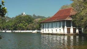 KANDY, SRI LANKA - FEBRUAR 2014: Ansicht des Hauses auf Kandy See mit Buddha-Statue im Hintergrund stock footage
