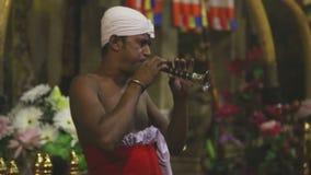 KANDY, SRI LANKA - FEBRUAR 2014: Ausführender, der eine traditionelle Flöte am Tempel des Zahnes spielt stock footage
