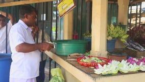 KANDY, SRI LANKA - FEBRUAR 2014: Bemannen Sie das Vereinbaren von Blumen nahe dem Tempel des Zahnes in Kandy Kandy ist eine bedeu stock video footage