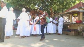 KANDY, SRI LANKA - FEBRUAR 2014: Die Einheimischen, die nahe dem Tempel des Zahnes in Kandy überschreiten Kandy ist eine bedeuten stock footage