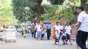 KANDY, SRI LANKA - FEBRUAR 2014: Die Einheimischen, die nahe dem Tempel des Zahnes in Kandy überschreiten Kandy ist eine bedeuten stock video