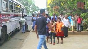 KANDY, SRI LANKA - FEBRUAR 2014: Einheimische, die am Busbahnhof nahe dem botanischen Garten in Kandy stehen stock footage