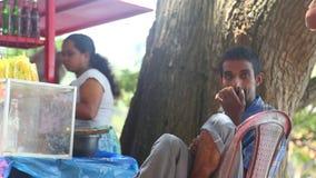 KANDY, SRI LANKA - FEBRUAR 2014: Frau, die an einem Stand nahe dem Tempel des Zahnes in Kandy arbeitet Kandy ist eine bedeutende  stock video footage