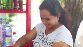 KANDY, SRI LANKA - FEBRUAR 2014: Frau, die an einem Stand nahe dem Tempel des Zahnes in Kandy arbeitet Kandy ist eine bedeutende  stock footage