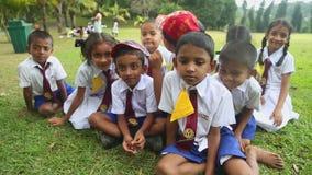 KANDY, SRI LANKA - FEBRUAR 2014: Gruppe Kinder Sri Lankan in der Schuluniform, die in den botanischen Gärten spielt Alle Kinder A stock footage