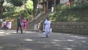 KANDY, SRI LANKA - FEBRUAR 2014: Leute, die nahe dem Tempel des Zahnes in Kandy überschreiten Kandy ist eine bedeutende Stadt in  stock video