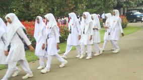 KANDY, SRI LANKA - FEBRUAR 2014: Moslemisches Schulmädchenschlangestehen im botanischen Garten in Kandy stock footage