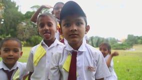 KANDY, SRI LANKA - FEBRUAR 2014: Porträt von Kindern Sri Lankan in der Schuluniform, die in den botanischen Gärten spielt Alle Ki stock footage