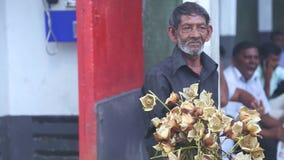 KANDY, SRI LANKA - FEBRUAR 2014: Schließen Sie herauf die Ansicht des Mannes Blumen nahe dem botanischen Garten in Kandy verkaufe stock video footage