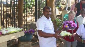 KANDY, SRI LANKA - FEBRUAR 2014: Schließen Sie herauf die Ansicht des Mannes Blumen nahe dem Tempel des Zahnes in Kandy verkaufen stock video footage