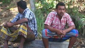 KANDY, SRI LANKA - FEBRUAR 2014: Zwei Elefantwächter, die nahe dem Tempel des Zahnes in Kandy sitzen stock video