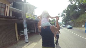 KANDY, SRI LANKA - FEBRUARY 2014: Man carrying little blond girl on his shoulders while walks down the street. stock video footage